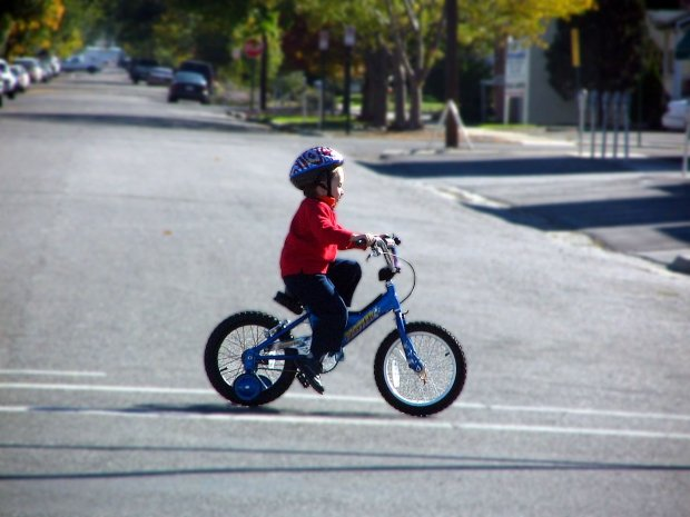 child on bike with training wheels