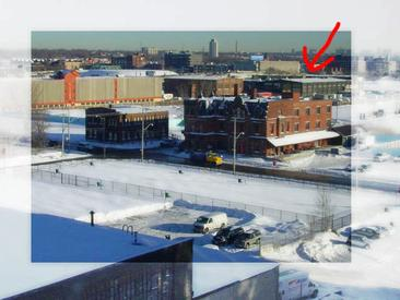 View of the Canary District from a building on Mill Street to the southwest. Arrow indicates the machine shop of the Dominion Wheel & Foundries Co. The Foundry building is to the left of it. Canary Restaurant is in front.